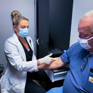lab technician drawing patient's blood